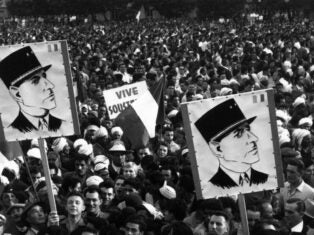 A crowd of Algerian demonstrators outside Government House, carrying Charles de Gaulle posters during the Algerian war of independence.