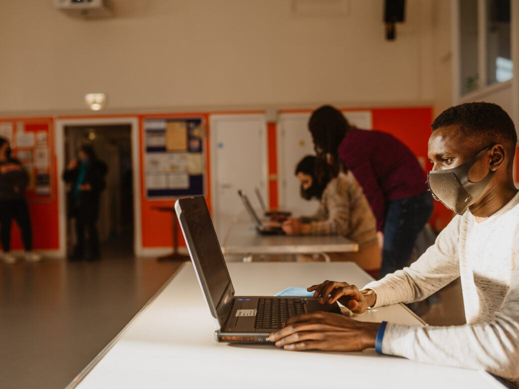A teenage boy wearing a mask and using a laptop