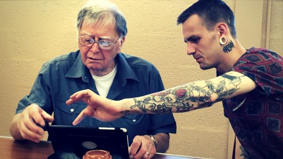 A digital champion teaching an older man how to use an iPad