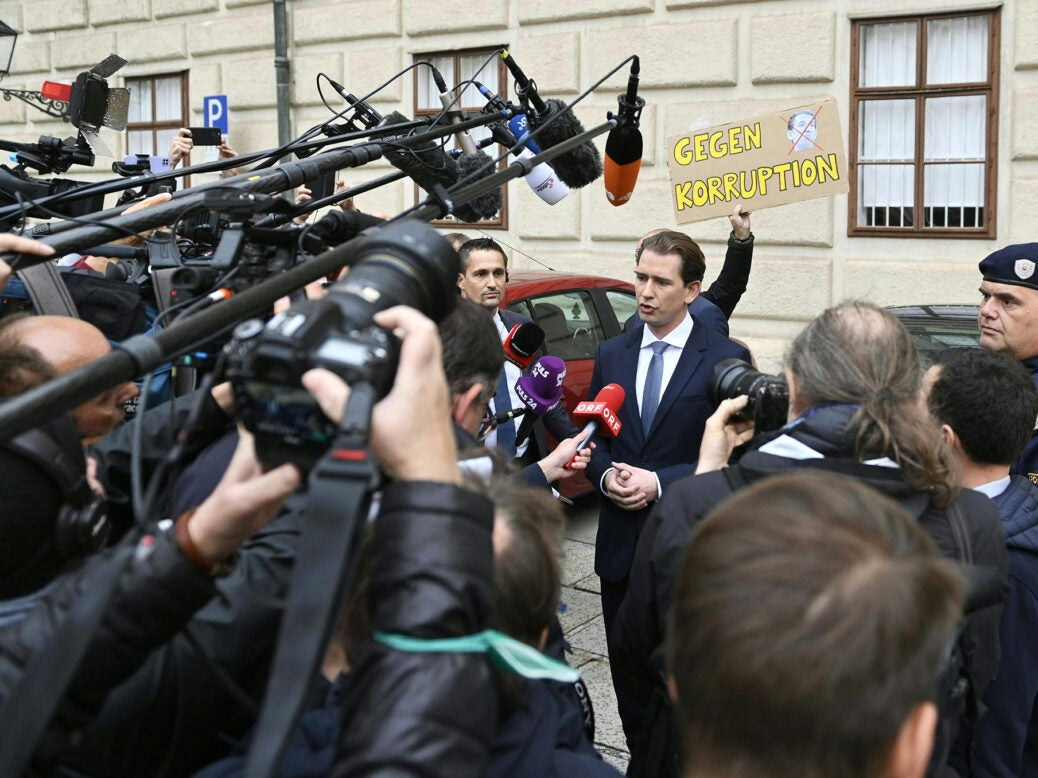 """Sebastian Kurz speaks to the media outside the Hofburg Palace, Vienna, as a protester holds a placard reading """"Against corruption"""" in the background"""